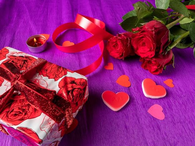 Rotes geschenk und rote rosen, band, brennende kerze auf lila hintergrund