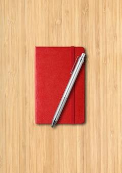 Rotes geschlossenes notizbuch mit einem stift