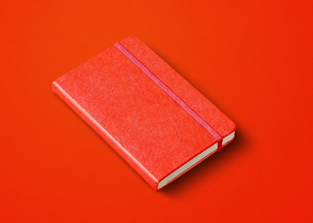 Rotes geschlossenes notizbuchmodell lokalisiert auf farbigem hintergrund