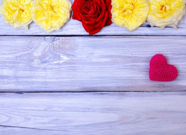 Rotes gestricktes herz auf einem weißen hölzernen hintergrund