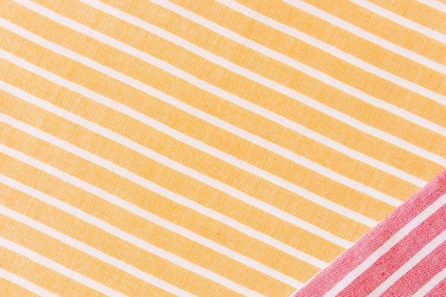 Rotes gewebe auf gelber und weißer streifentextiltischdecke
