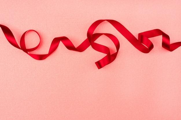 Rotes gewelltes band auf rosa hintergrund. party dekoration