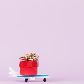 Rotes giftbox mit goldenem Bogen über dem Spielzeugflugzeug gegen rosa Hintergrund