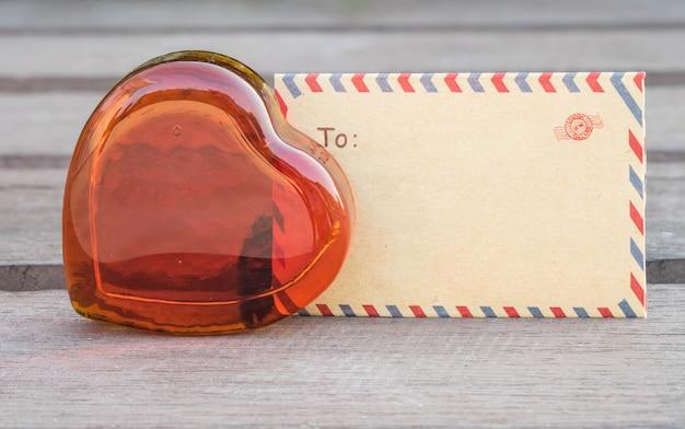 Rotes glas der nahaufnahme in der herzform mit braunem umschlag auf unscharfem holzstuhl im valentinsgrußthema