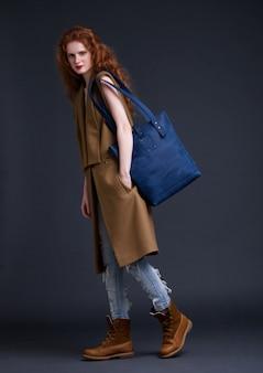 Rotes haarmode-modell, das große blaue ledertasche auf dunklem hintergrund hält. mädchen, das lange ärmellose jacke mit jeans und stiefeln trägt.