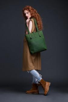 Rotes haarmode-modell, das große grüne ledertasche auf dunklem hintergrund hält. mädchen, das lange ärmellose jacke mit jeans und stiefeln trägt.