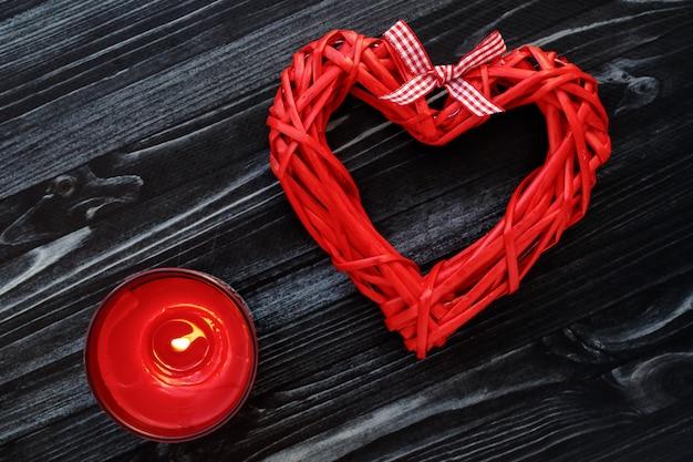 Rotes handgemachtes herz auf dunklem hölzernem hintergrund. brennende kerze auf tafel. valentinstag geschenkkarte. symbol der liebe, romantikkonzept.