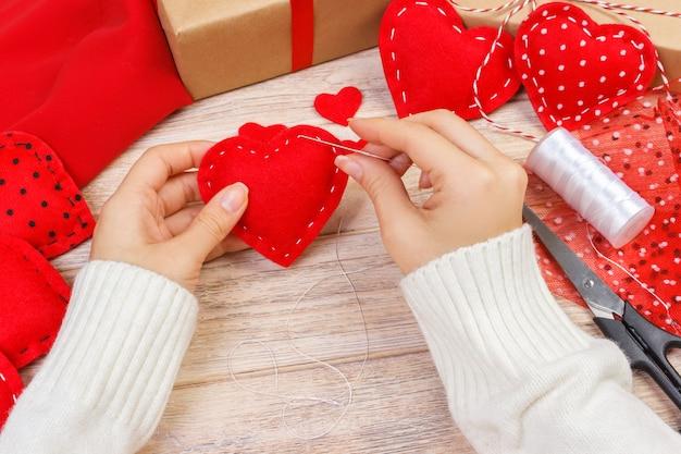 Rotes handgemachtes herz-förmiges weiches spielzeug, valentinstag, romantisches verhältnis, gesunder lebensstil, schönes geschenk, liebe und gesundheitswesenkonzept. urlaub schmücken valentinstag