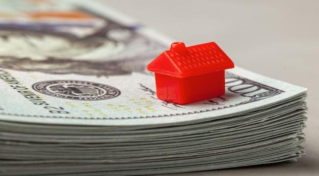 Rotes haus auf einem stapel geld das konzept des kaufs oder der versicherung von immobilien.