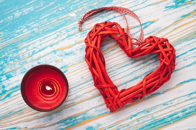 Rotes hausgemachtes herz und brennende kerze auf blauem hölzernem hintergrund. romantische festliche geschenkkarte am valentinstag. symbol der liebe, romantischer hintergrund.