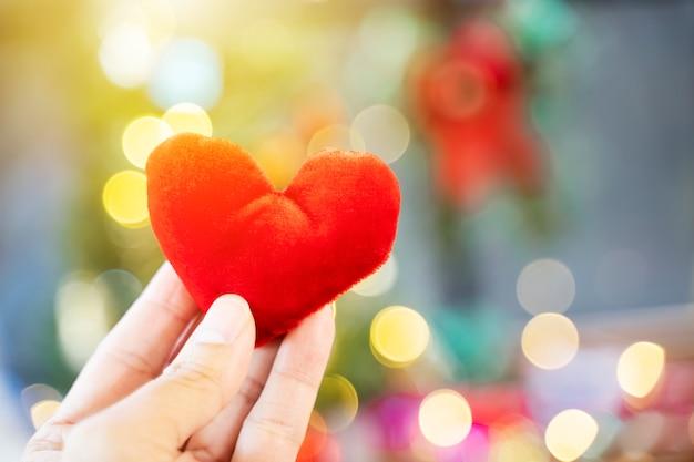 Rotes herz an hand mit unscharfem hellem hintergrund. liebe, hochzeit und valentinsgrußkonzept.