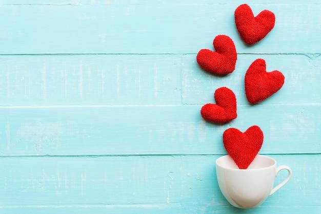 Rotes herz auf blauem hölzernem hintergrund für liebes- und valentinsgrußtageskonzept.