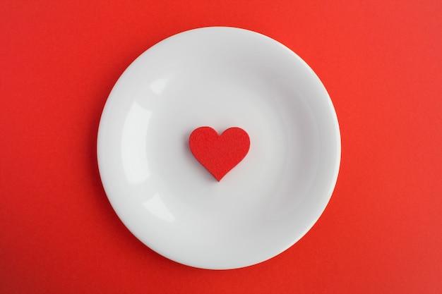 Rotes herz auf der weißen platte auf der roten oberfläche.