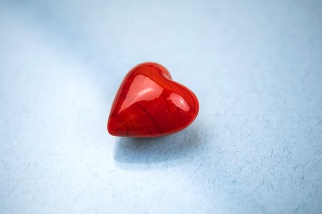 Rotes herz auf einem glas, blauer hintergrund, konzept der liebe und einsam, valentinstagfoto
