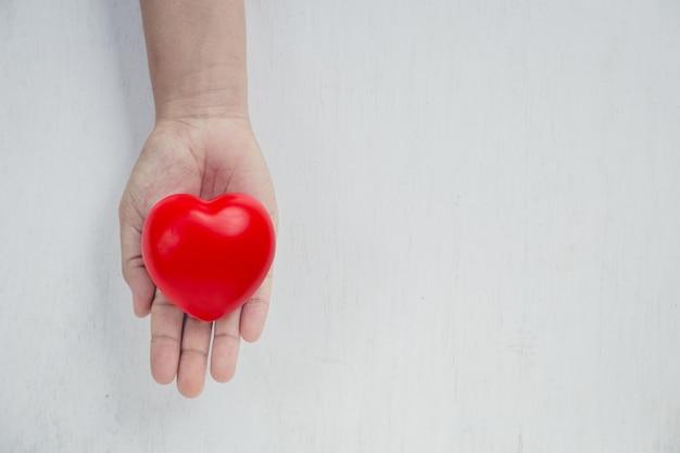 Rotes herz auf mädchenhand