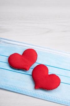 Rotes herz auf medizinischen gesichtsmasken. konzeptunterstützung, liebe, fürsorge und ein dankeschön an die mitarbeiter an vorderster front und im gesundheitswesen