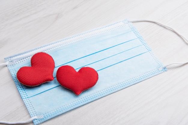 Rotes herz auf medizinischen gesichtsmasken. konzeptunterstützung, liebe, fürsorge und ein dankeschön an die wichtigsten mitarbeiter des gesundheitswesens. glücklicher valentinstag. pandemie, quarantäne coronavirus. valentinstag.