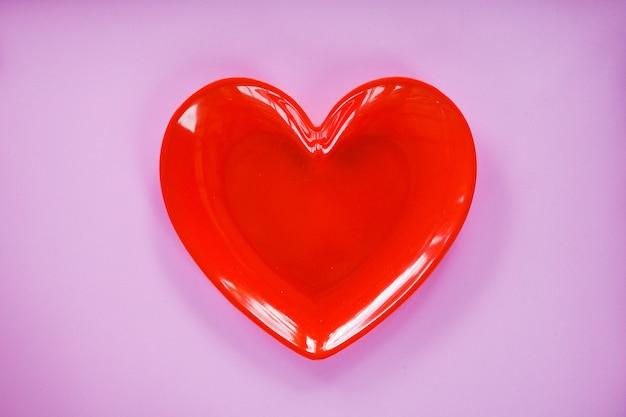 Rotes herz auf romantischem liebeskonzept des rosa- / valentinsgrußessens - romantisches gedeck