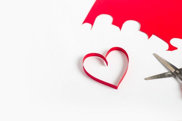 Rotes herz aus papier, schere und farbigem karton auf hellweißem hintergrund geschnitten. zusammensetzung valentinstag. banner. flache lage, draufsicht.