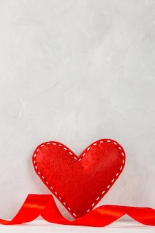 Rotes herz, band gegen eine weiße wand, konzept, eine postkarte für valentinstag.
