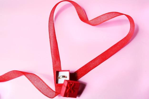 Rotes herz-band mit roter verlobungsring-box zum valentinstag. platz kopieren.