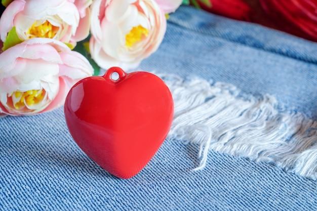 Rotes herz, das auf alten und tränenblauen jeans liegt. valentinstag konzept.