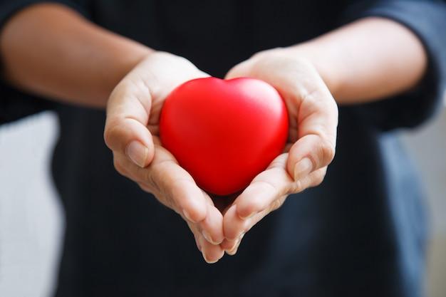 Rotes herz, das von beiden händen der frau gehalten wird, stellt helfende hände dar, die sich sorgen, liebe, sympathie