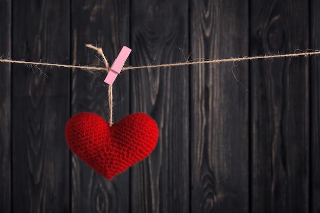 Rotes herz des valentinsgrußes auf seil auf hölzernem hintergrund