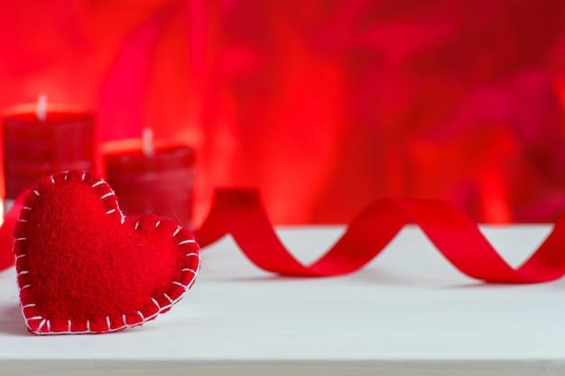Rotes herz des valentinsgrußtages mit rosen und kerzen