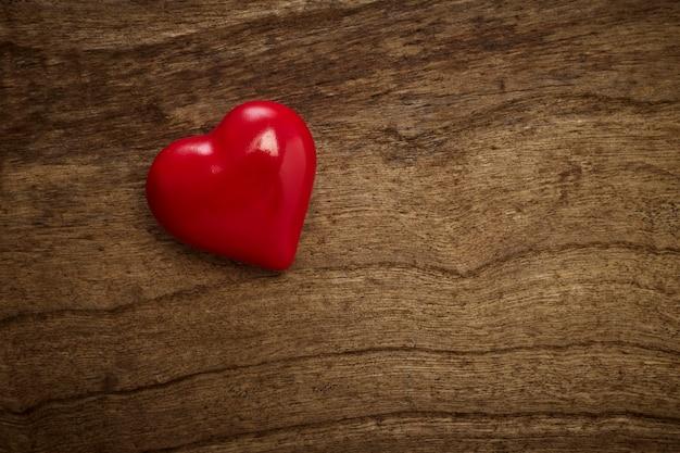 Rotes herz des valentinstags auf altem holz, draufsicht