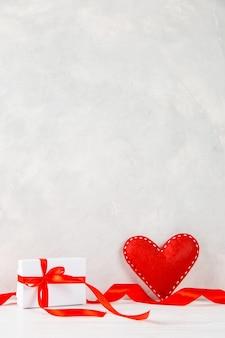 Rotes herz, geschenk, band gegen die einer weißen wand, konzept, eine postkarte für valentinstag.