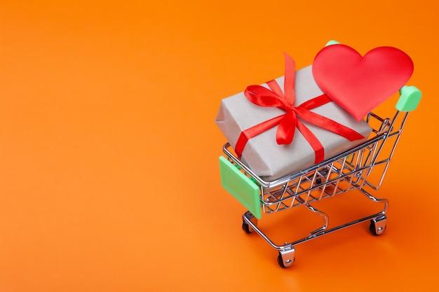 Rotes herz, geschenkbox mit rotem band im mini-einkaufswagen