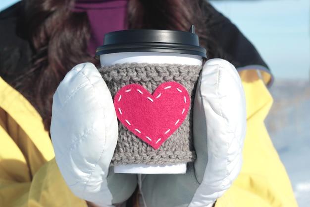 Rotes herz gestrickte kaffeetasse gemütlich in weißen handschuhen.