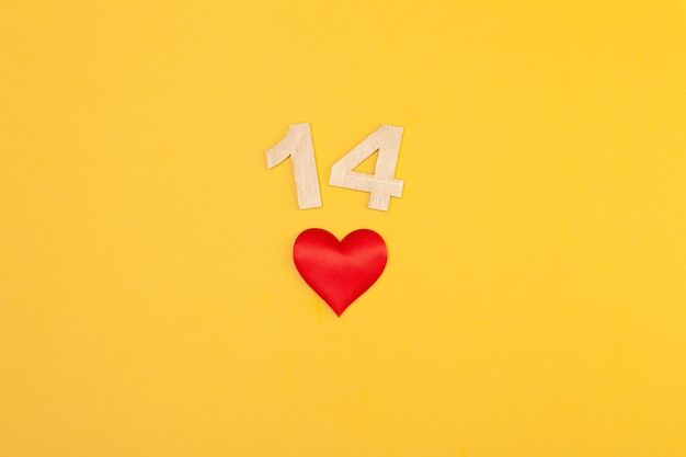 Rotes herz, goldene zahlen 14 auf gelbem hintergrund, grußkarte februar valentinstag, liebeshintergrund, romantik, horizontal, kopierraum, flach