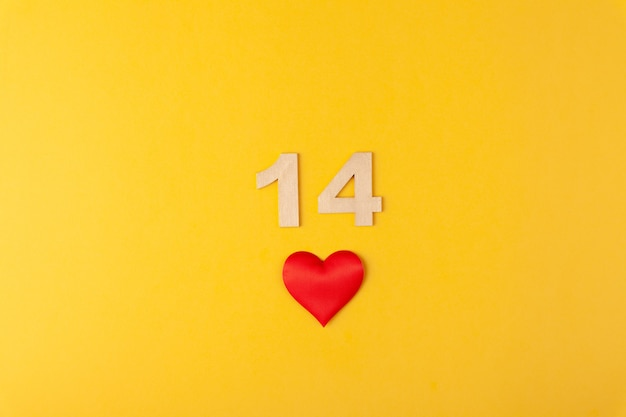 Rotes herz, goldene zahlen 14 auf gelbem hintergrund, grußkarte februar valentinstag, liebeshintergrund, romantik, horizontal, kopierraum, flache lage