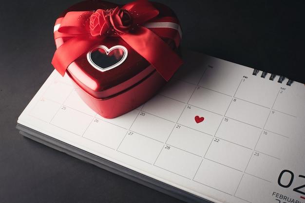Rotes herz im februar 14 auf dem kalender mit herz formte geschenkbox, valentinstagkonzept.