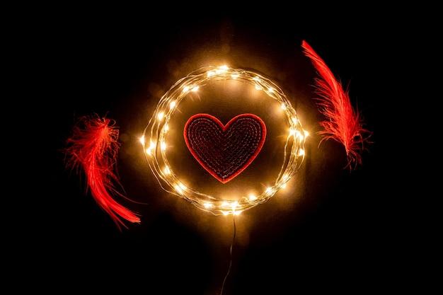 Rotes herz im kreis der feiertagsfeier-lichtgirlande mit roten federn. valentinstag-konzept.