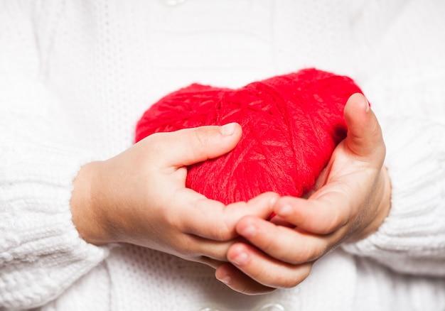 Rotes herz in den händen eines kleinen kindes in weißer bluse