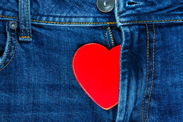 Rotes herz in der fliege der jeans. hintergrund für den valentinstag.