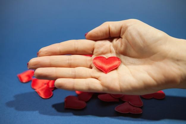 Rotes herz in der handfläche eines mädchens auf einem blauen hintergrund.