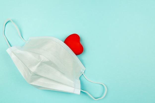 Rotes herz in der medizinischen schutzmaske auf hellblauem hintergrund, draufsicht. kreative wohnung lag mit kopierraum.