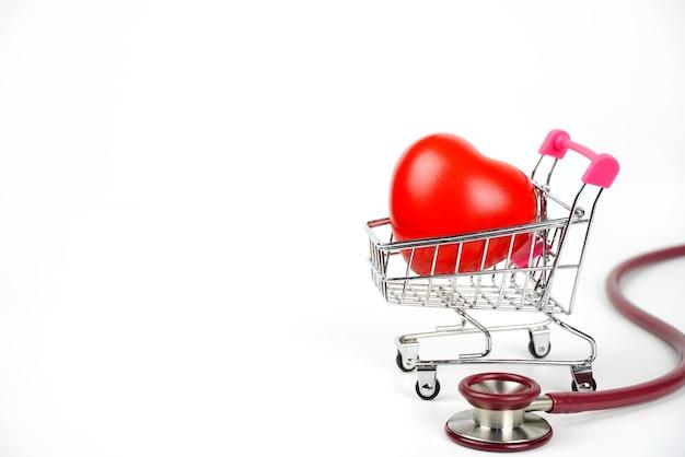 Rotes herz in einem einkaufswagen und einem stethoskop das konzept der medizin und krankenversicherung.