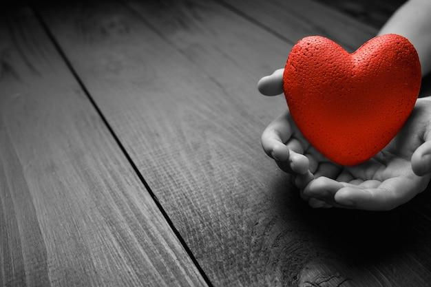 Rotes herz in händen an einer dunklen wand, das konzept der liebe und fürsorge für geliebte und bedürftige. schwarz und weiß.