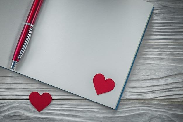 Rotes herz-kugelschreiber-leeres notizbuch auf holzbrettausbildung