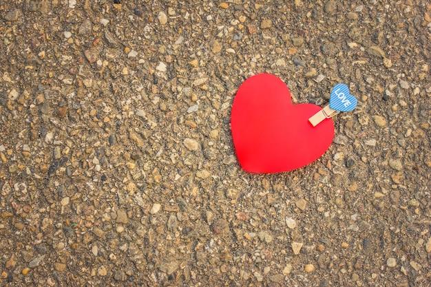 Rotes herz liegt auf dem bürgersteig. ein kleines blaues herz, das an ein großes rotes herz gebunden ist. konzept valentinstag