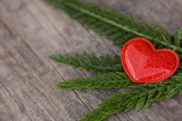 Rotes herz liegt auf einem hölzernen hintergrund mit grünen blättern