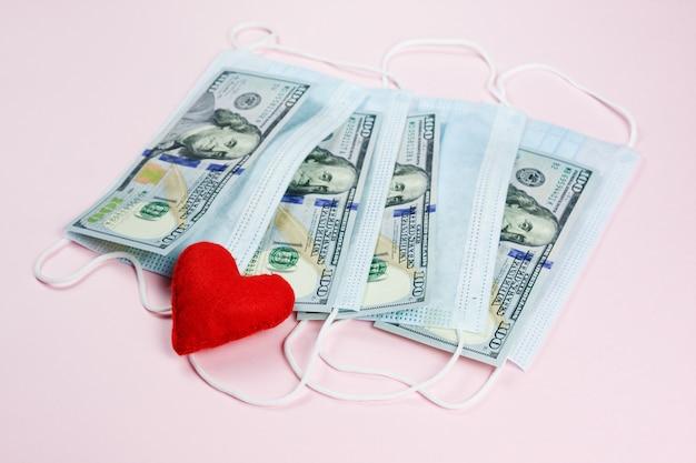 Rotes herz, medizinische masken und dollars auf pink. hilfe für länder mit geld und masken. finanzkrise