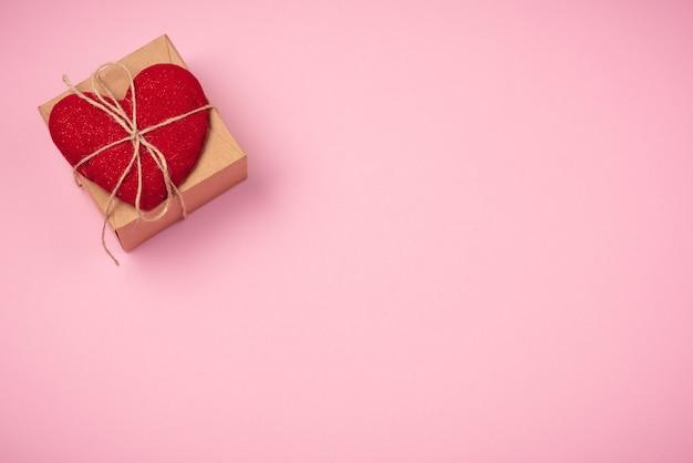 Rotes herz mit einem geschenk zum valentinstag auf einem schönen rosa hintergrund. herzanhänger.