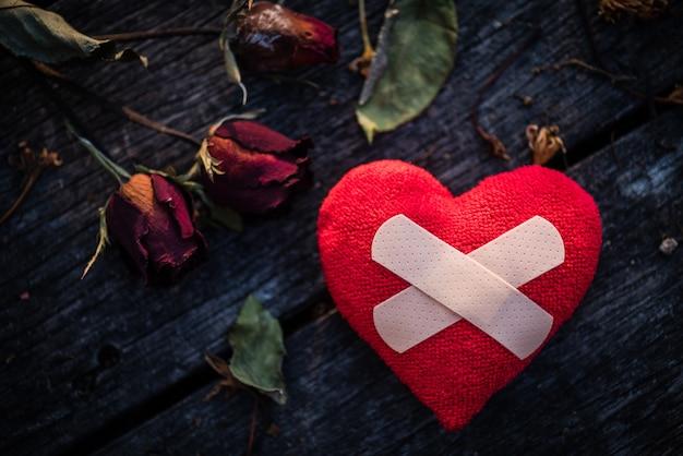 Rotes herz mit getrockneter rotrose auf hölzernem hintergrund. herz gebrochen, liebe und valentines.