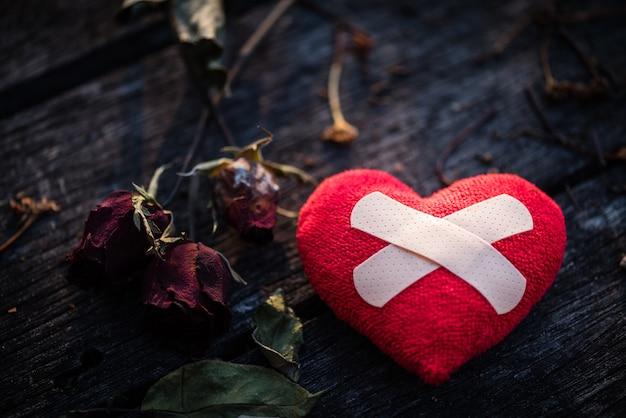 Rotes herz mit getrockneter rotrose auf hölzernem hintergrund. herz gebrochen, liebe und valentinstag